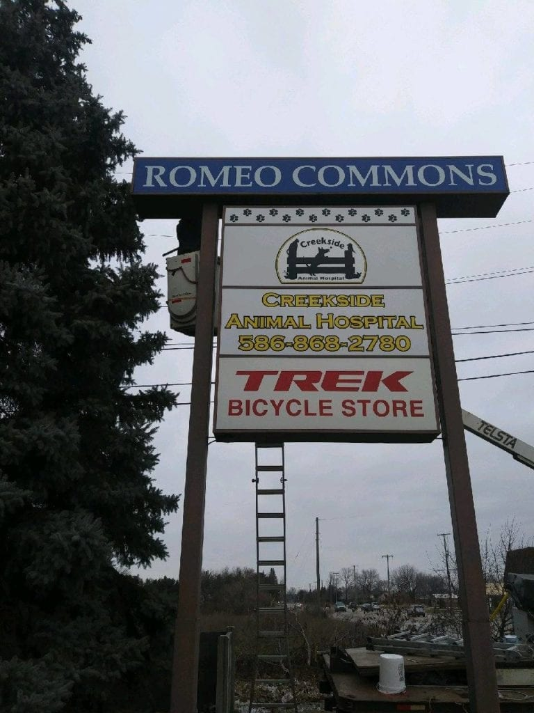 "Romeo Commons Double Pole Pylon Sign "" Creekside Animal Hospital"" "" Trek Bicycle Store"" Faces"