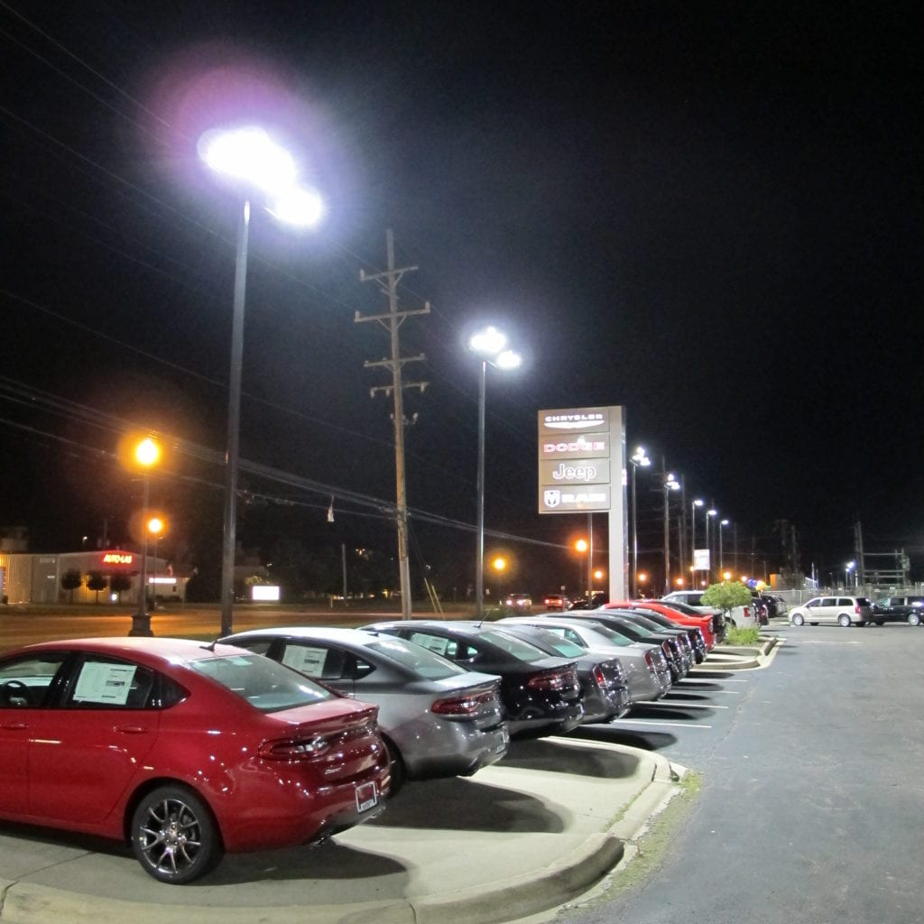 McInerneys Car Dealership Lot Lighting pictured with row of cars and pylon road sign