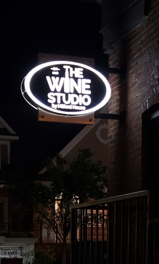 The Wine Studio Blade sign night view illuminating push-thru storefront