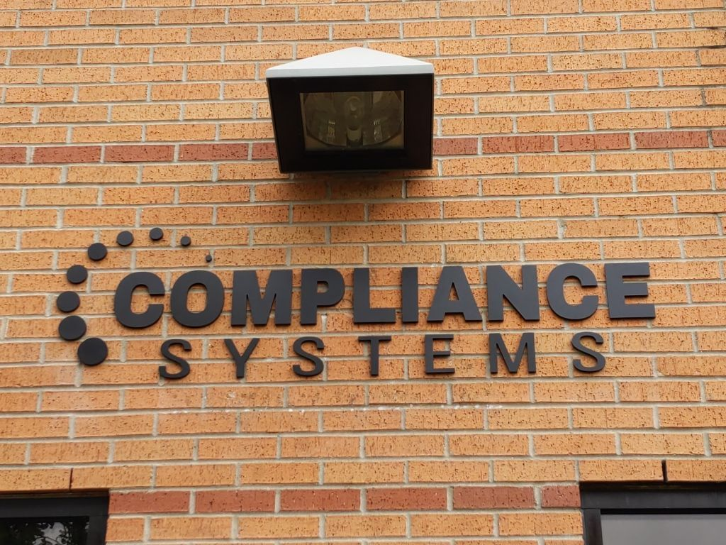 "Compliance Systems logo dimensional matte black 3/8"" acrylic exterior letters sign storefront brick building external lighting overhead lamp spot light"